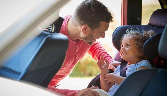 Father Securing Daughter Into Car Seat