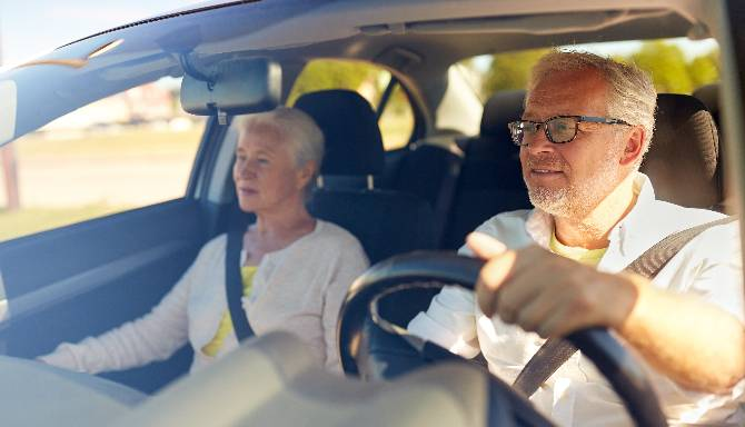 Pensioner couple driving a car
